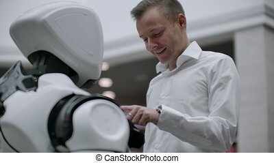 A man in a shirt communicates with a white robot asking...