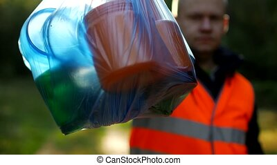 A man in a signal orange vest holds a package with garbage on the background of nature, forest, close-up, garbage collection, a janitor, volunteer