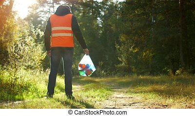 A man in a signal orange vest is standing with a package of...