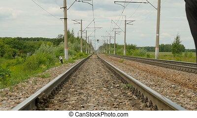 A man in a sporty uniform walking on rails