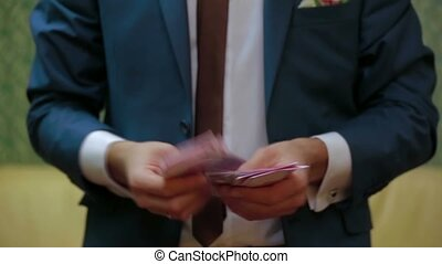 A man in a suit recounts money Ukrainian Hryvnia