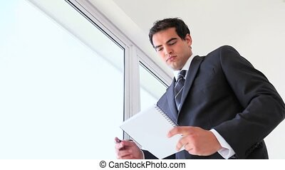 A man in a suit walks to the window with a notepad
