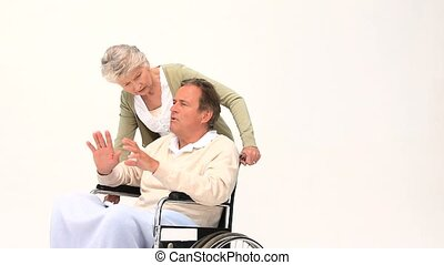 A man in a wheelchair having a massage of his wife isolated...