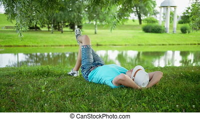 A man in a white hat is resting lying on the grass in a city park
