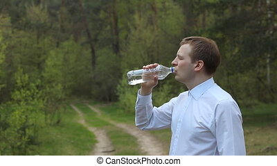 A man in a white shirt drinking water from a bottle in the...