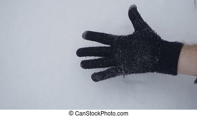 A man in a winter glove shows different gestures in the snow, close-up