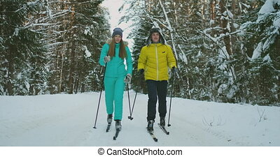 A man in a yellow jacket and a woman in a blue jumpsuit in...