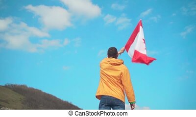 A man in a yellow jacket, blue jeans and glasses is standing in the mountains and waving the Canadian flag.