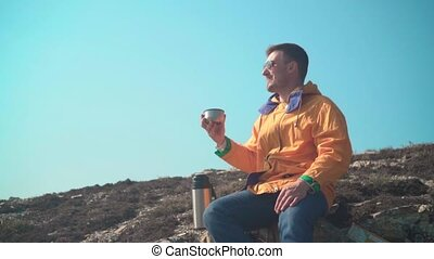A man in a yellow jacket, blue jeans and glasses sits in the mountains, enjoys the scenery, drinks tea from a thermos.