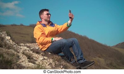 A man in a yellow jacket, blue jeans and glasses sits in the mountains, enjoys the scenery, shoots video on the phone.