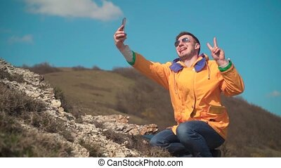 A man in a yellow jacket, blue jeans and glasses sits in the mountains, enjoys the scenery, takes a selfie, photographs.