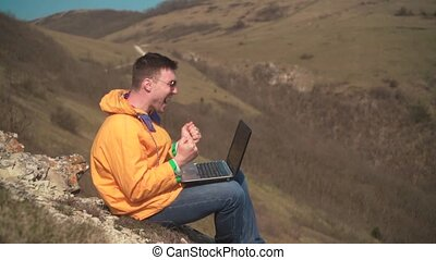 A man in a yellow jacket, blue jeans and glasses sits in the mountains, works at a laptop and rejoices, emotions of joy.