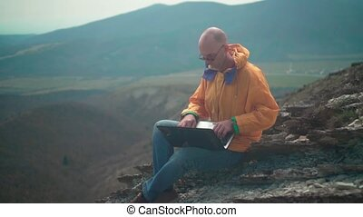 A man in a yellow jacket, blue jeans and glasses sits on the edge of a cliff and works on a laptop.