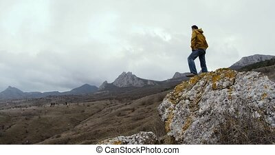 A man in a yellow jacket stands on a stone against a...