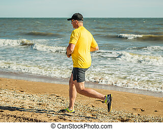 A man in a yellow shirt do fitness by the sea on a hot day.