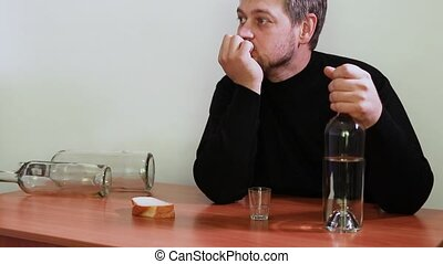 A man in alcoholic intoxication sits at a table and holds a bottle of alcoholic beverage. Vodka, delirium, dependence on alcohol.