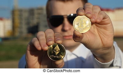 A man in black glasses is holding a bitcoin and etherium,...