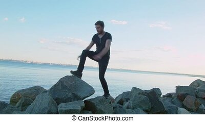 A man in black jumps over rocks by the sea.