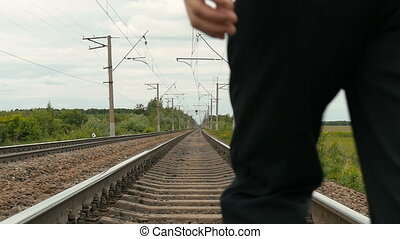 A man in business clothes is running along the railway tracks. slow motion