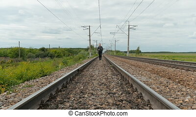 A man in business clothes is running on rails, holding a laptop in his hands.