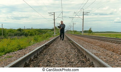 A man in business clothes is walking on rails. Works on a laptop.