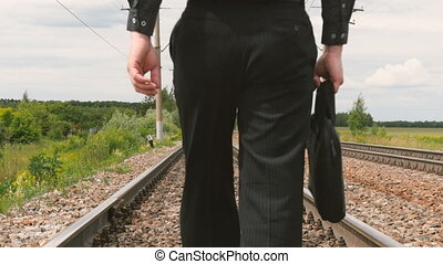 A man in business clothes is walking on rails.