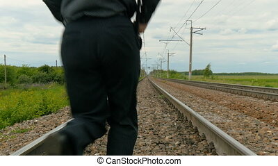 A man in business clothes with a laptop running on rails.