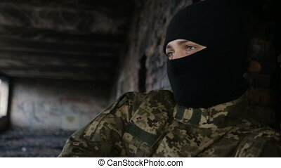 A man in camouflage and a black mask on an old abandoned building
