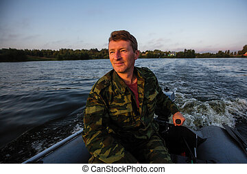 A man in camouflage controls a motor boat on the lake.