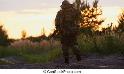 A man in camouflage suit with arms out into the distance. Airsoft game