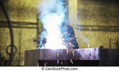 A man in defense works with a welding machine - sparks fly...