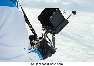 a man in gloves is holding a professional remote control with a screen for tracking from a quadrocopter against the background of a snowy field
