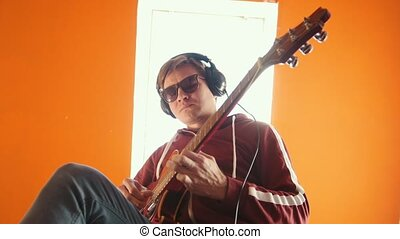 A man in headphones wearing glasses playing guitar in the studio