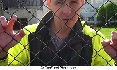 A man in his 20's, leaning against the fence looking at the camera