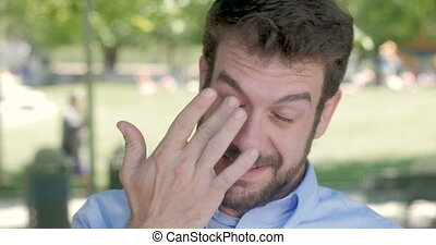 A man in his early 30s rubbing his eye outside