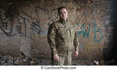 A man in military uniform on an abandoned building