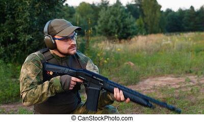 A man in military uniform with a gun shooting