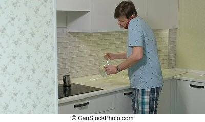 A man in pajamas drinking water in the kitchen. Morning - A...