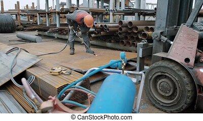 A man in protective uniform and a helmet on his head sawing a large steel part in order to put it on a recycling