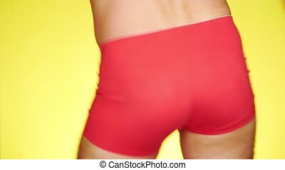 a man in red boxers dancing on a yellow background....