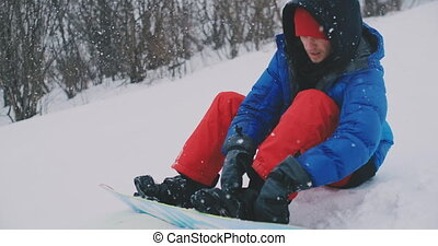 A man in red pants sitting on the snow fastens snowboard...