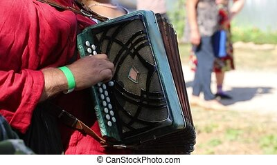 A man in russian folk costumes plays accordion in nature....