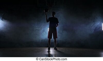 A man in sports form rotates a basketball on his finger...