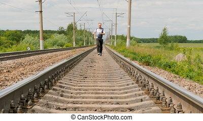A man in sports uniforms runs on rails. He follows his health, runs cross, active life style.