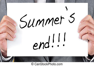 a man in suit holding a blackboard with the sentence summers end written in it