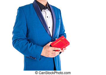 A man in suit holding red present box over white background