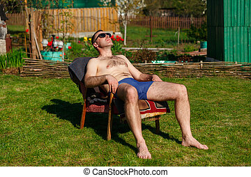 A man in swimming trunks sunbathes