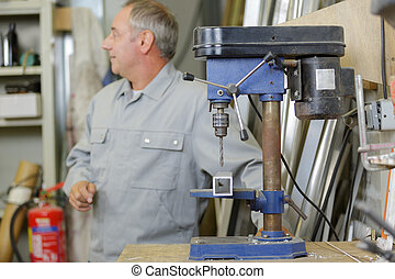 a man in the background using a milling machine