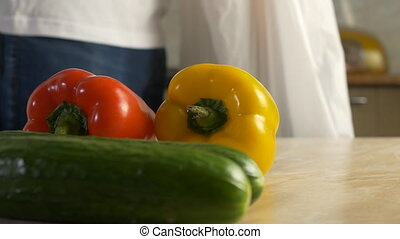 A man in the kitchen is shopping for package vegetables,...