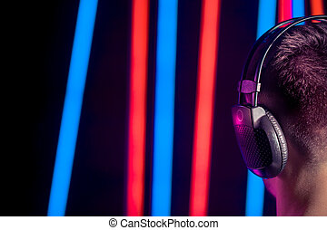 A man in the Studio headphones, close-up. Rear view. On blurred background of colored lights.